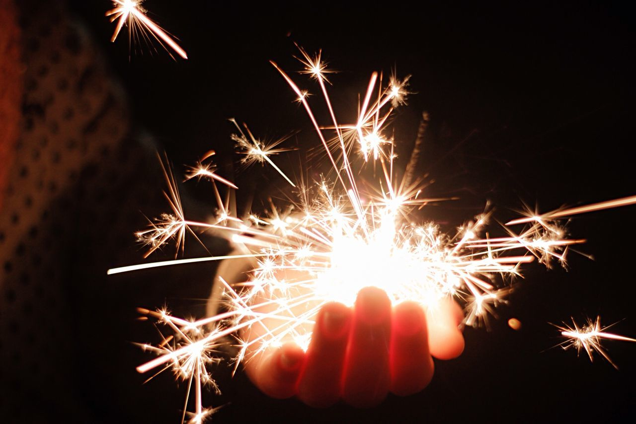 Cropped image of person holding lit sparkler at night
