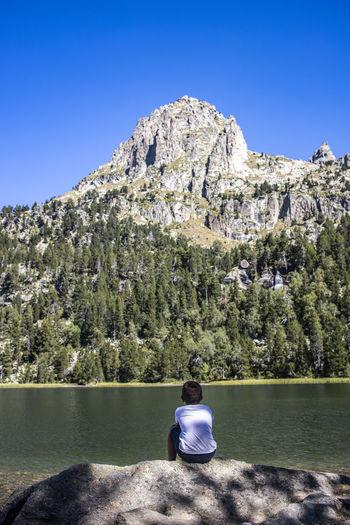 Little boy resting near a lake looking a big mountain