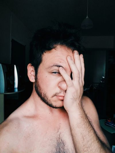 Close-up portrait of shirtless young man covering face with hand at home