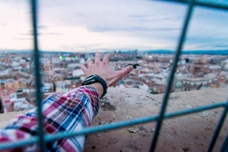 hand stretches to the horizon to freedom outside cage concept One Person Architecture Building Exterior City Human Body Part Lifestyles Built Structure Leisure Activity Sky Real People Day Cityscape Human Hand Relaxation Nature Outdoors Window Hand Body Part Human Arm Concept Fredom Cage