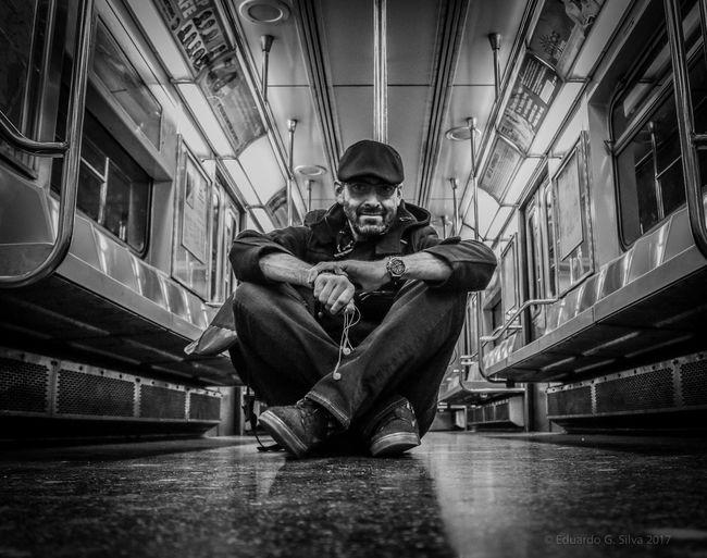 Full length of man sitting in subway train