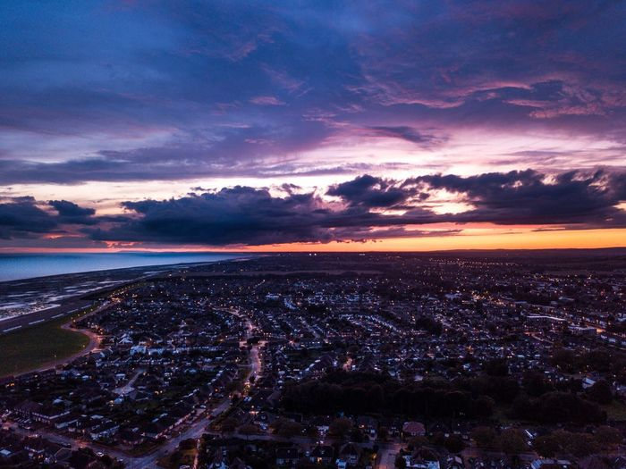 Aerial view of city against sky at sunset
