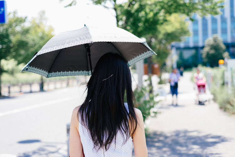 Rear View Of Woman Walking Under Umbrella During Sunny Day In City