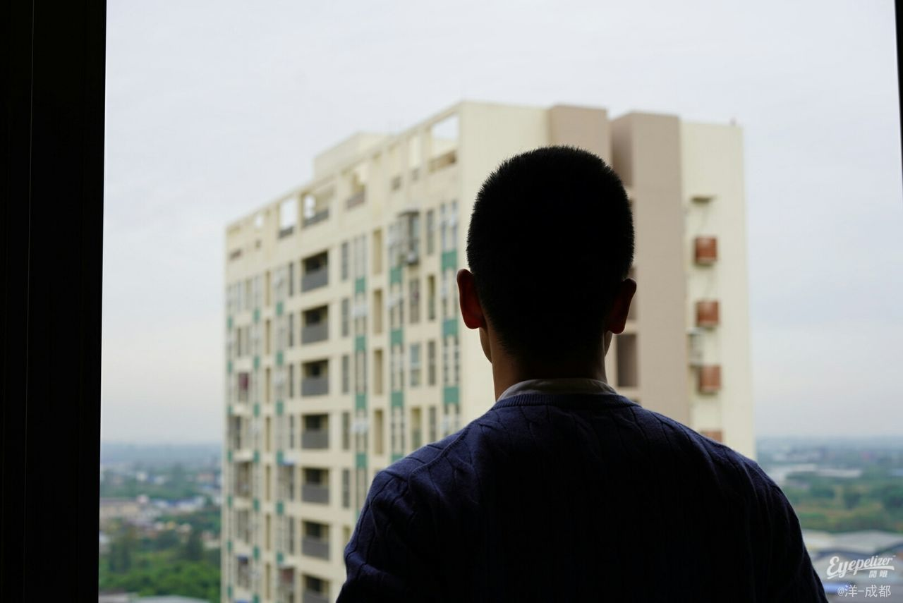 rear view, one person, headshot, real people, men, built structure, building exterior, portrait, architecture, leisure activity, lifestyles, outdoors, focus on foreground, window, day, sky, standing, building, nature, looking at view