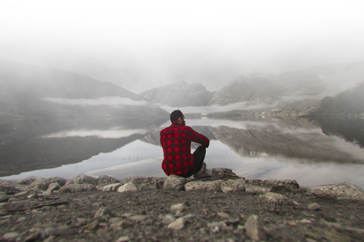 Man Norway Beauty In Nature Environment Fog Looking At View Mountain One Person Outdoors Rear View Rock Scenics - Nature Solitude Tranquil Scene Tranquility Vacations Water
