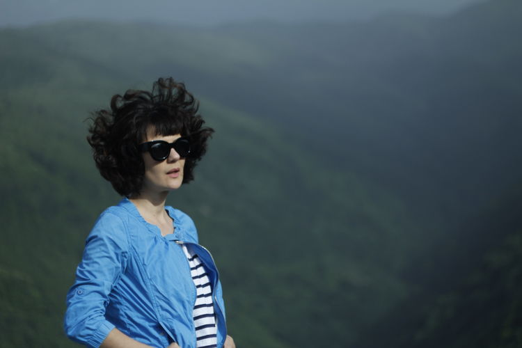 Woman wearing sunglasses standing against mountains