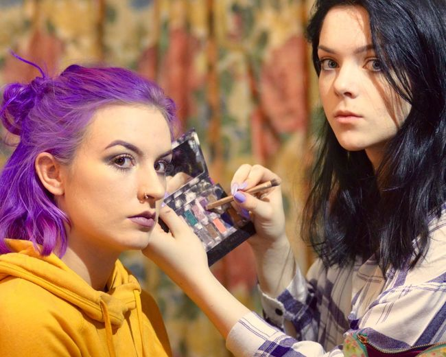 Portrait Of Beautician Applying Make-Up On Woman