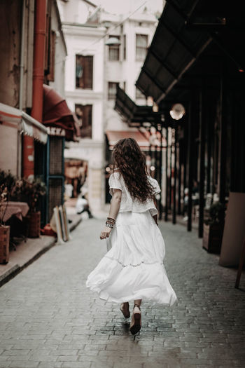 Young hippie girl in a white dress running down the street of istanbul