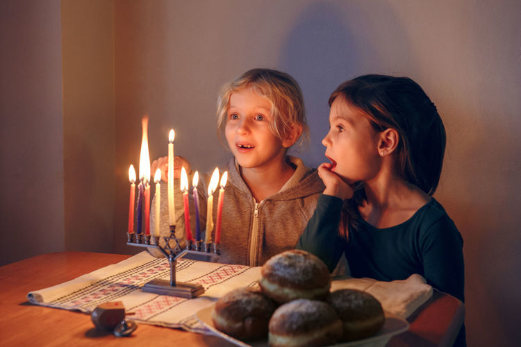 Girls friends lighting candles on menorah for traditional winter jewish hanukkah holiday at home