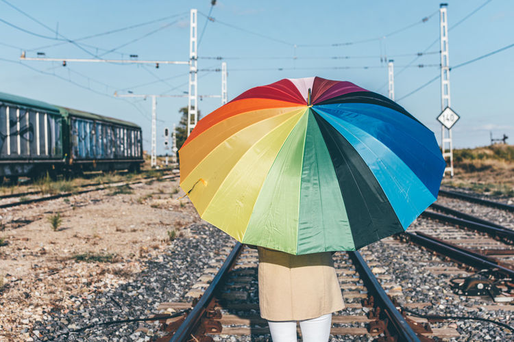 Low angle view of person standing by railroad track against sky
