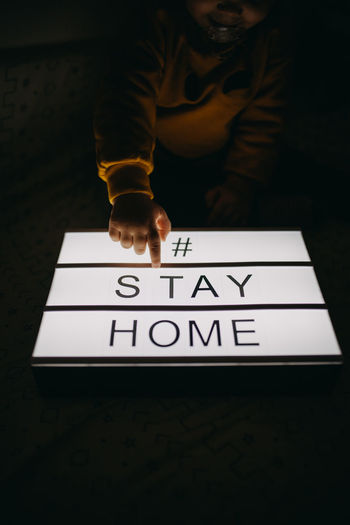 Girl touching light box with text stay home in darkroom