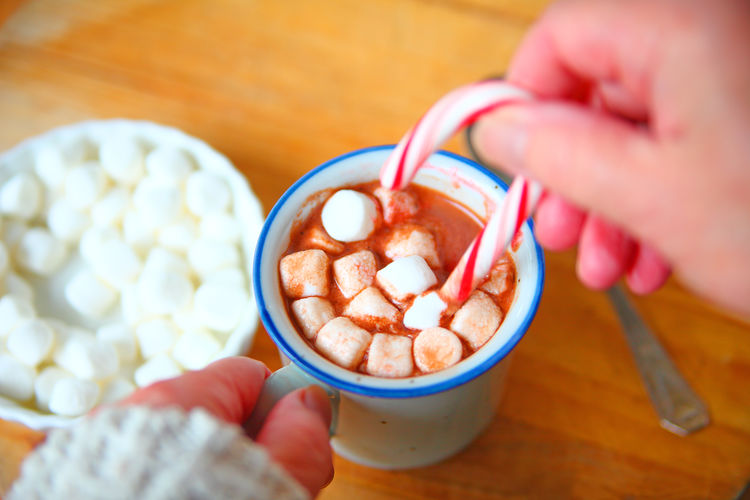 Woman with hot cocoa and marshmallows Food And Drink One Person Holding Snack Temptation Indulgence Refreshment Close-up Indoors  Hands Woman Winter Hot Drink Point Of View POV Marshmallows Candy Cane Holidays Christmas Sweet Food Sweater