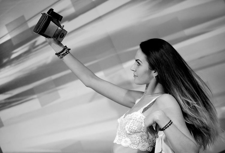 Young woman taking selfie from camera while leaning on retaining wall