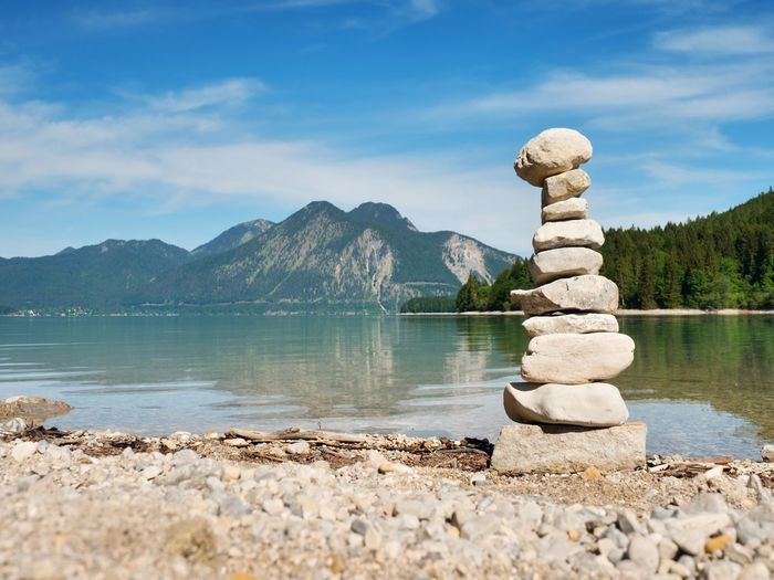 Stack of stones in lake against sky