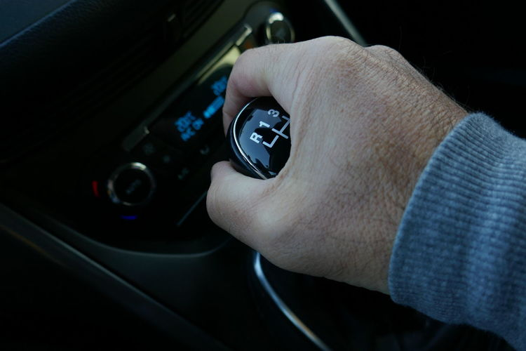 Cropped image of hand shifting gear in car