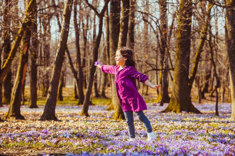 Full length of girl standing against trees