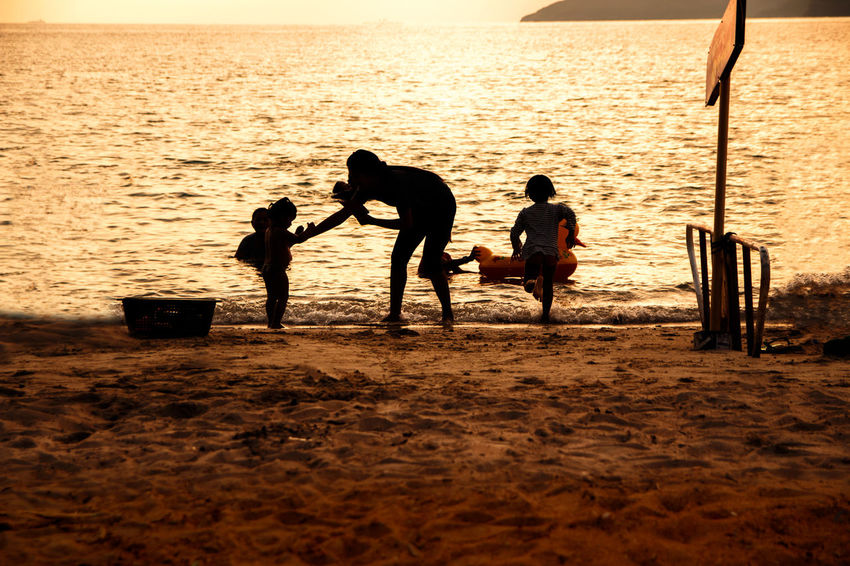 silhouette of people at the beach,The beauty of natural light at sunset. Sea Beach Water Group Of People Land Real People Sky Silhouette Nature Lifestyles Togetherness Sunset Full Length Horizon Over Water Child Men Playing Scenics - Nature Outdoors Silhouette Happiness Happy People Holiday Relaxing Children Women Man Romantic Orange Clouds And Sky Love Family Summer Sunrise Boy Freshair Freedom Fun