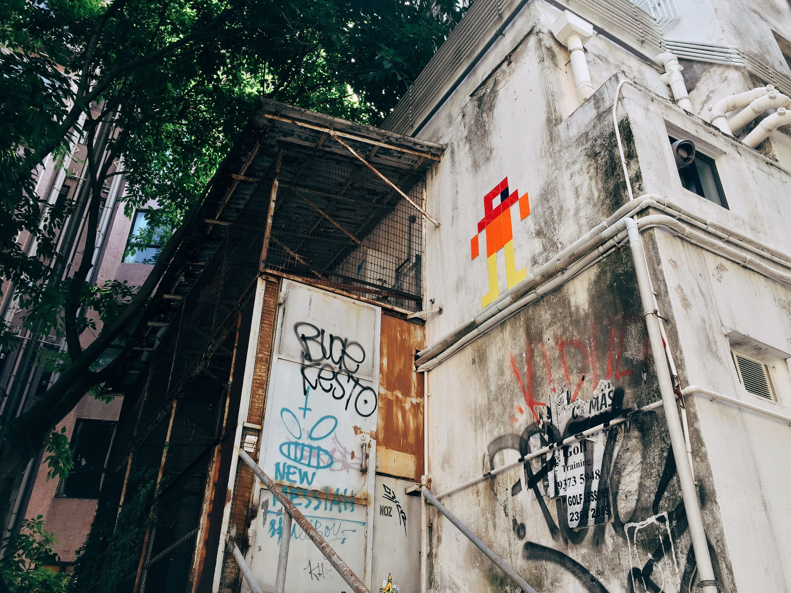 architecture, built structure, building exterior, text, low angle view, western script, graffiti, communication, window, building, day, capital letter, wall - building feature, no people, outdoors, sign, non-western script, information, art and craft, brick wall