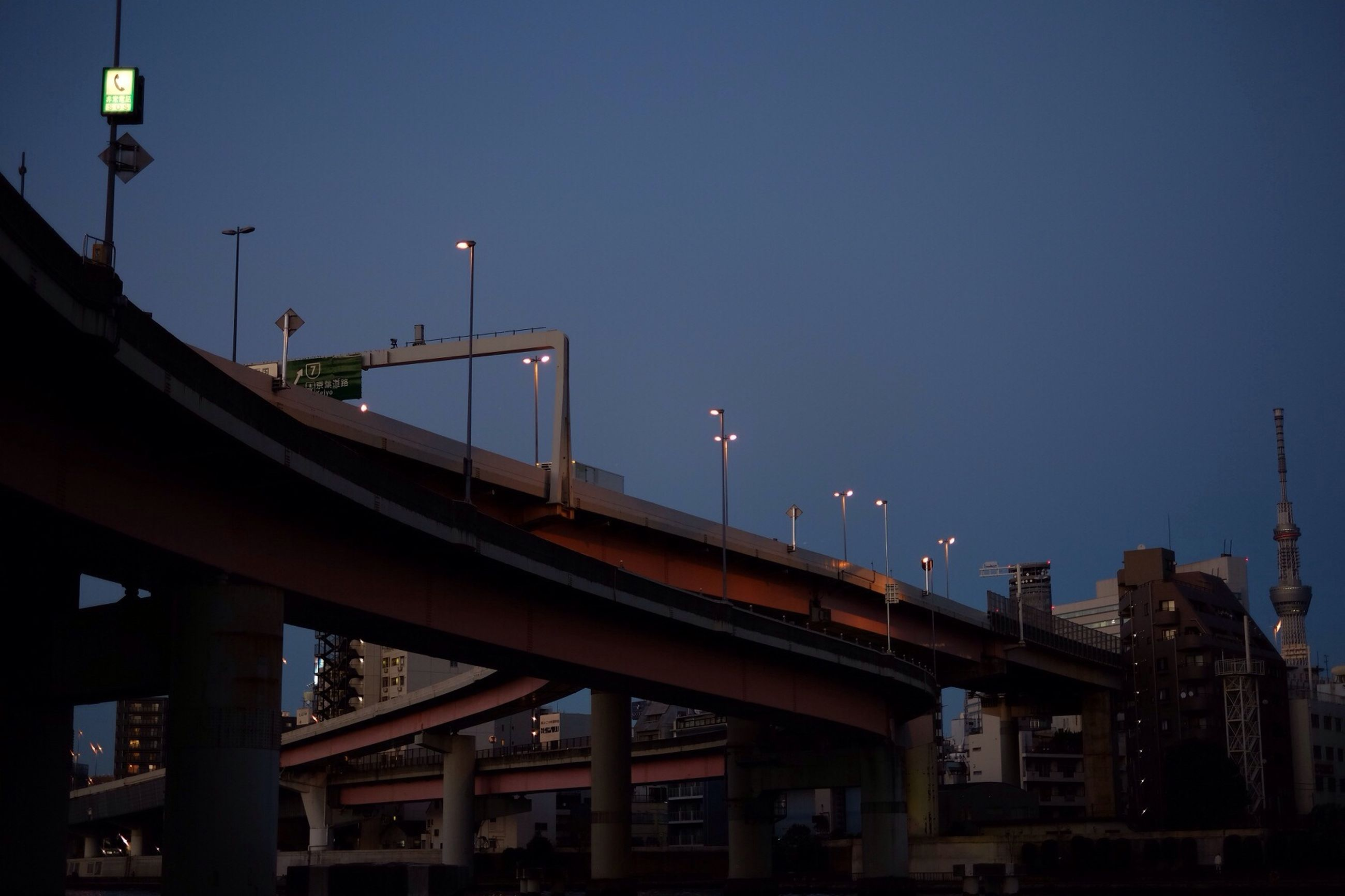 illuminated, built structure, architecture, street light, lighting equipment, clear sky, night, low angle view, building exterior, copy space, sky, dusk, blue, moon, connection, electric light, railing, outdoors, bridge - man made structure, city