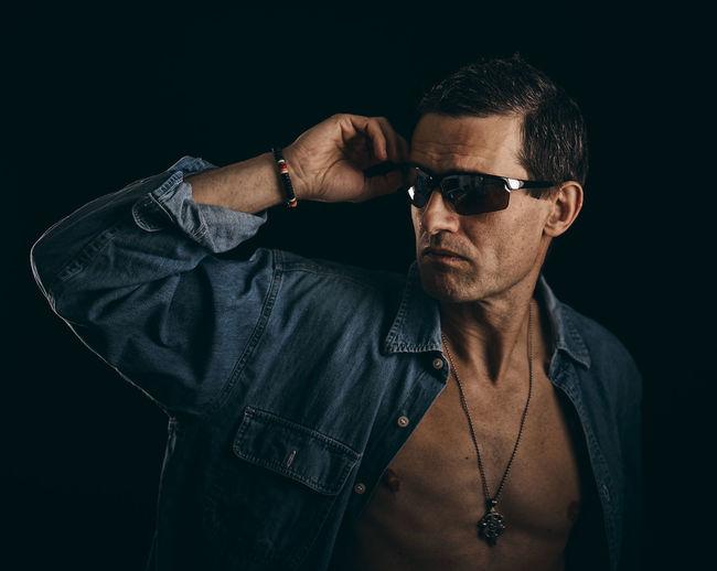 Man wearing sunglasses against black background