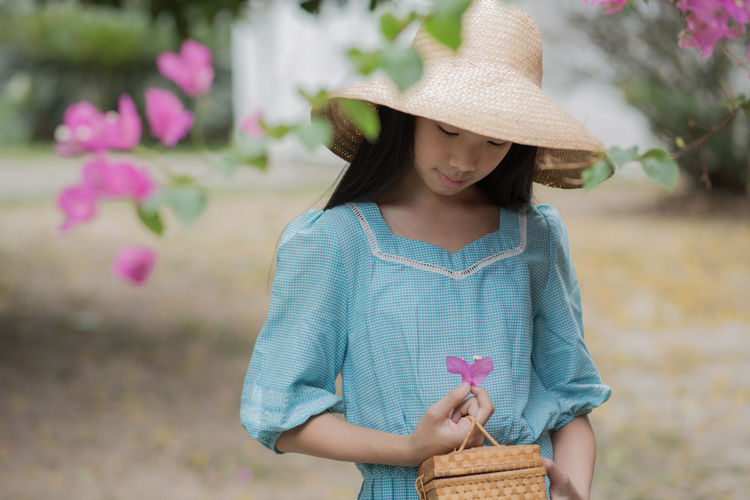Picking a Flower. Fashion Portrait girl in vintage old style. Asian  Basket Child Children Only Close-up Cute Day Fashion Flower Garden Girl Hat Human Body Part Nature Old-fashioned One Girl Only One Person Outdoors People Portrait Portrait Of A Woman Sun Hat Thai Vintage The Portraitist - 2018 EyeEm Awards