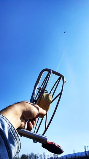 Cropped hand of man holding kite string against clear blue sky