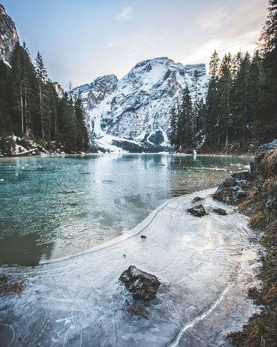 Scenic view of lake by snowcapped mountains against sky during winter