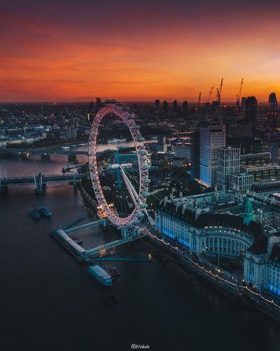 Illuminated ferris wheel in city at sunset