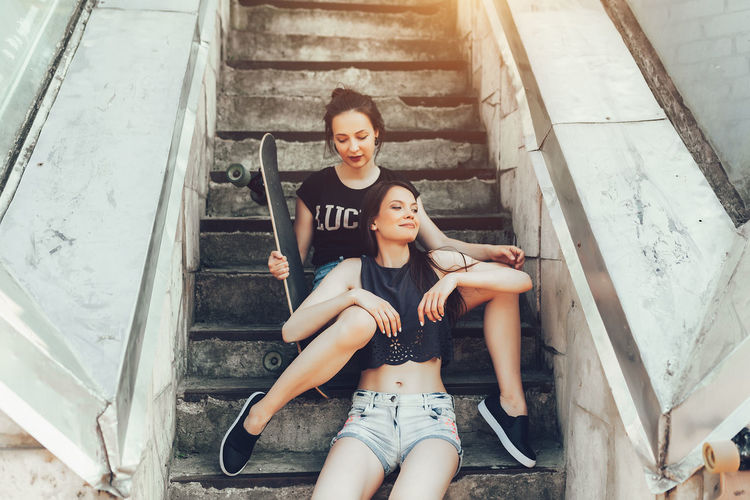 Smiling Woman Sitting With Friend Holding Skateboard On Steps
