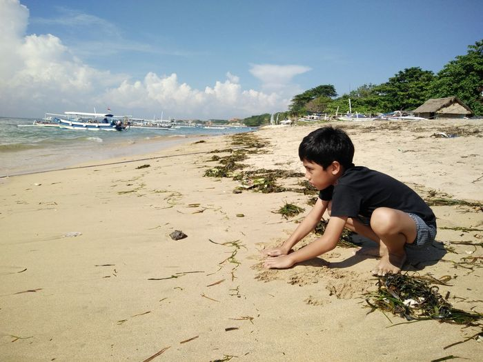 Beach Casual Clothing Childhood Day Full Length Horizon Over Water Leisure Activity Lifestyles Nature Outdoors Person Relaxation Sand Sea Shore Sitting Sky Tranquil Scene Tranquility Vacations Water Bali, Indonesia Tanjungbenoa Nusadua