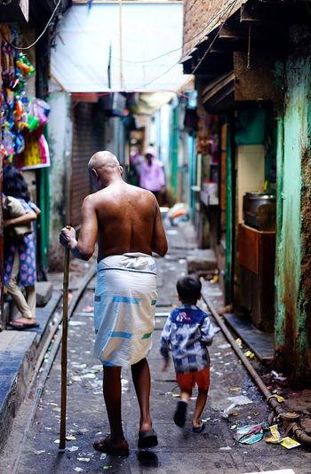 Inside The Dharavi Slum Mumbai Mumbai India Shirtless Trash Walkin Through Slum Walking Stick Older Man