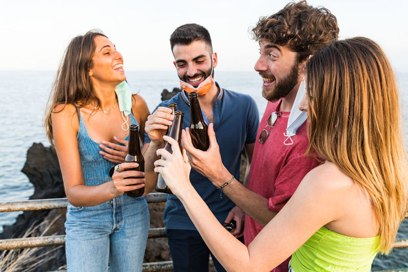 Smiling friends holding drinks standing outdoors