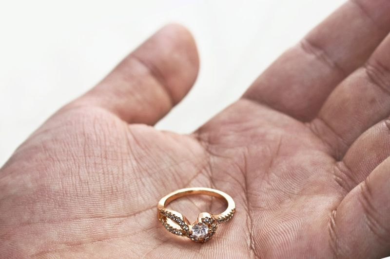 Cropped Hand Of Man Holding Diamond Ring Against White Background