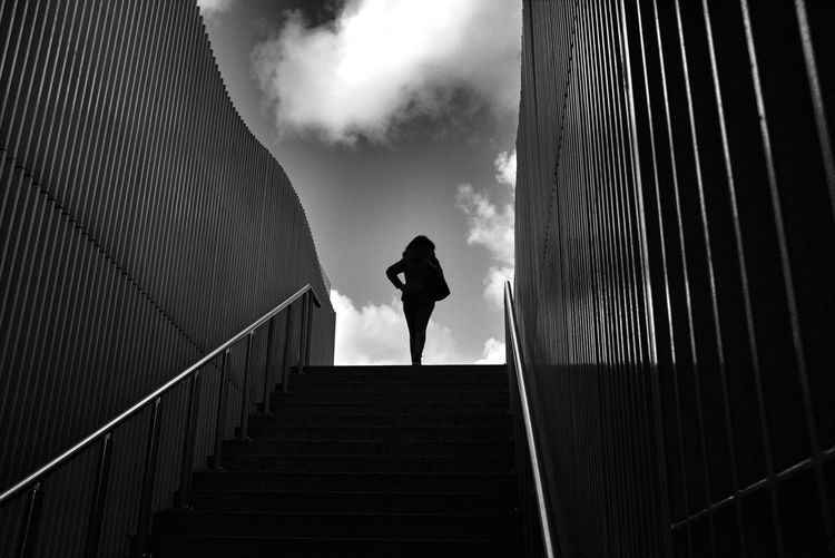 Low angle view of silhouette woman walking on steps against sky