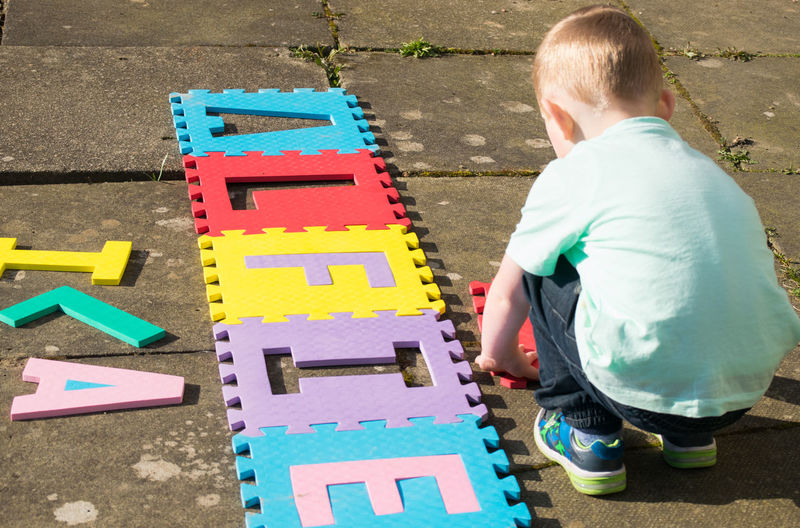 Child Outside Outdoors Real People One Person One Child From Behind Letters Learning Educational Colourful Kneeling Caucasian Day Horizontal Colour Image Childhood Playing Slabs Park - Man Made Space Jigsaw  Toys Playground Alfie Blonde