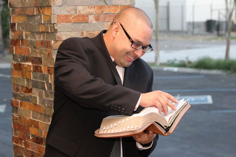Smiling mid adult man holding book while standing against architectural column