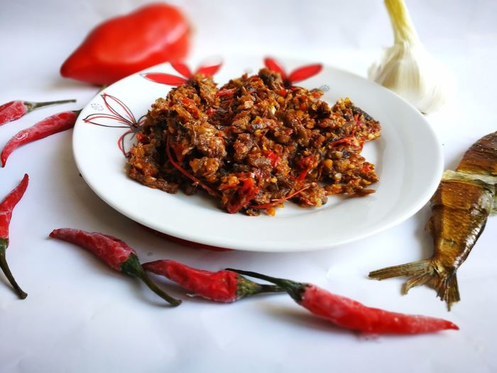 High angle view of food and chili peppers over white background