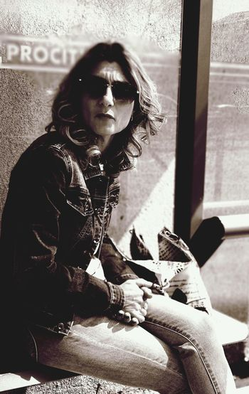Portrait of young woman wearing sunglasses sitting on window