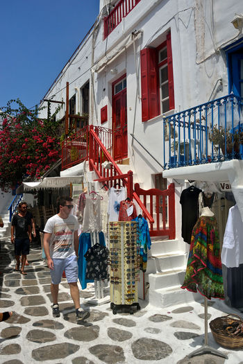 colored street view of Mykonos with people walking and tourist shops Building Exterior Architecture Built Structure Group Of People Women Real People City Men People Day Adult Leisure Activity Nature Sunlight Lifestyles Retail  Street Crowd Building Outdoors Buying Retail Display Shops Souvenirs/Gift Shop Greek Architecture Tourist Tourism Travel Travel Destinations Street View Streetphotography Red Windows White Buildings Bouganville Flower Summertime Clothes Shop Walking Around Shopping