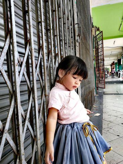 Cute Little Girl Standing Against Metallic Shutter