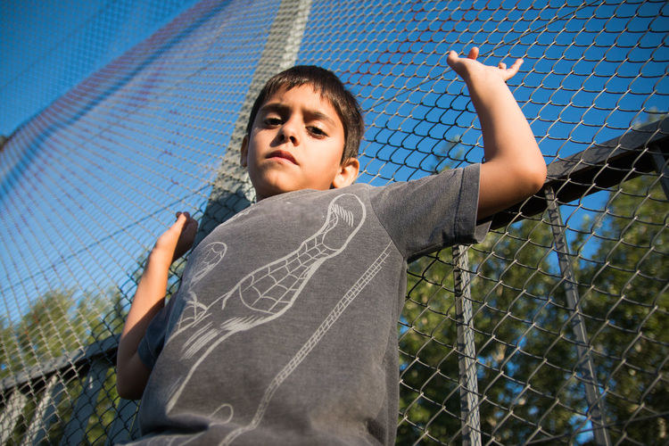 Portrait of boy standing against chainlink fence