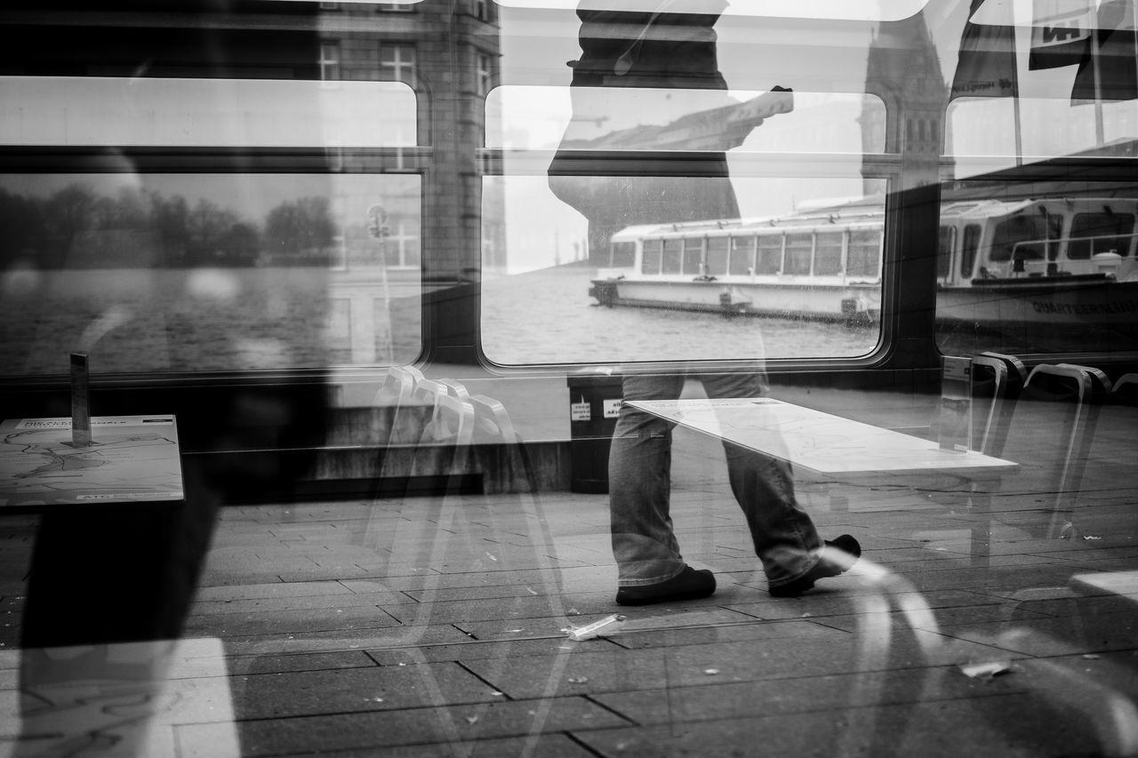 Reflection of man walking on bus window