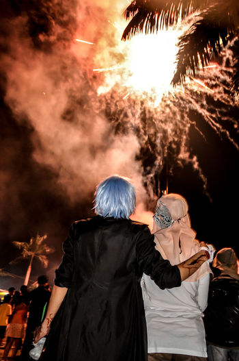 Rear view of young couple standing against firework display in sky at night