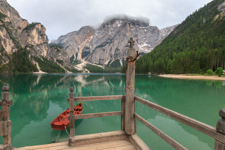 Scenic view of lake pragser wildsee lago di braies, against mountains with wooden boathouse in front