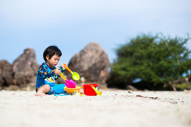 Boy playing with toys on sand