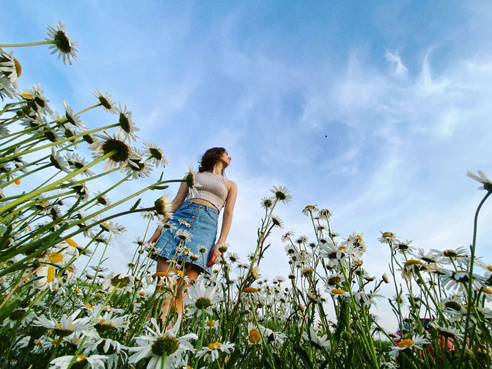 Low angle view of woman walking on field against sky