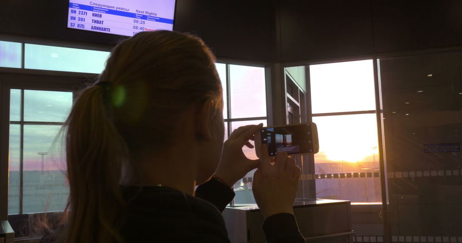 Portrait of woman photographing through window