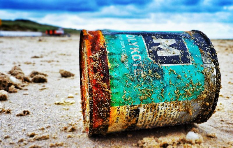 Close-up of abandoned tin can on shore