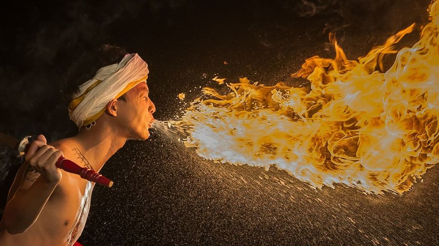 Side View Of Fire-Eater Over Black Background