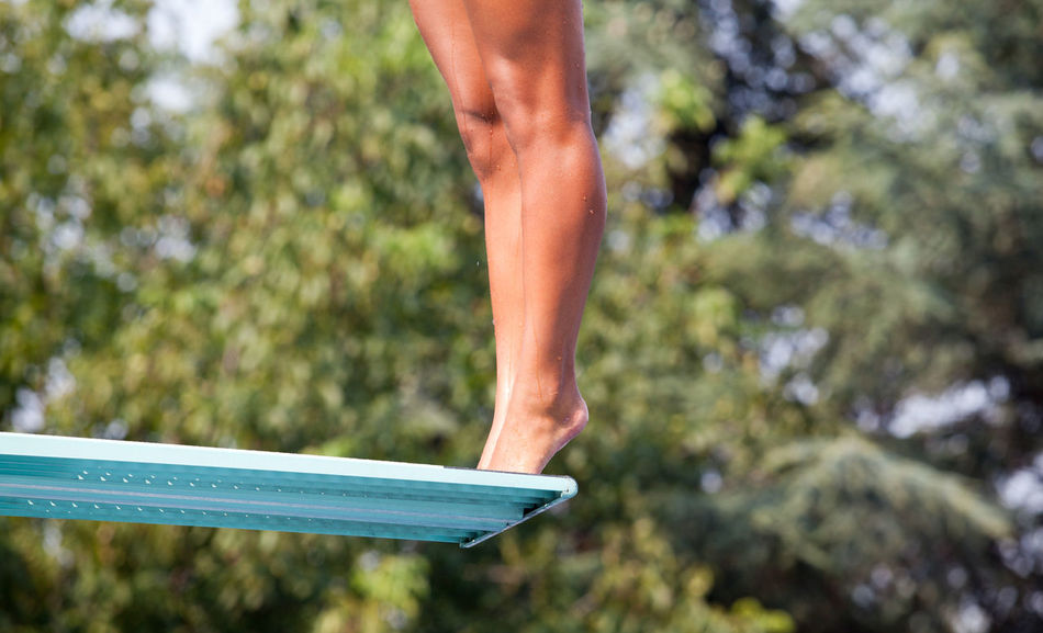 Female high diver standing on a springboard, preparing to dive Diving Holiday Jump Recreation  Standing Swimming Dive Diver Diving Board Feet Female Girl Human Leg Human Legs Jumping Leisure Activity Nature Outdoors Pool Sport Springboard Springboard Diver Summer Swimming Pool Vacation